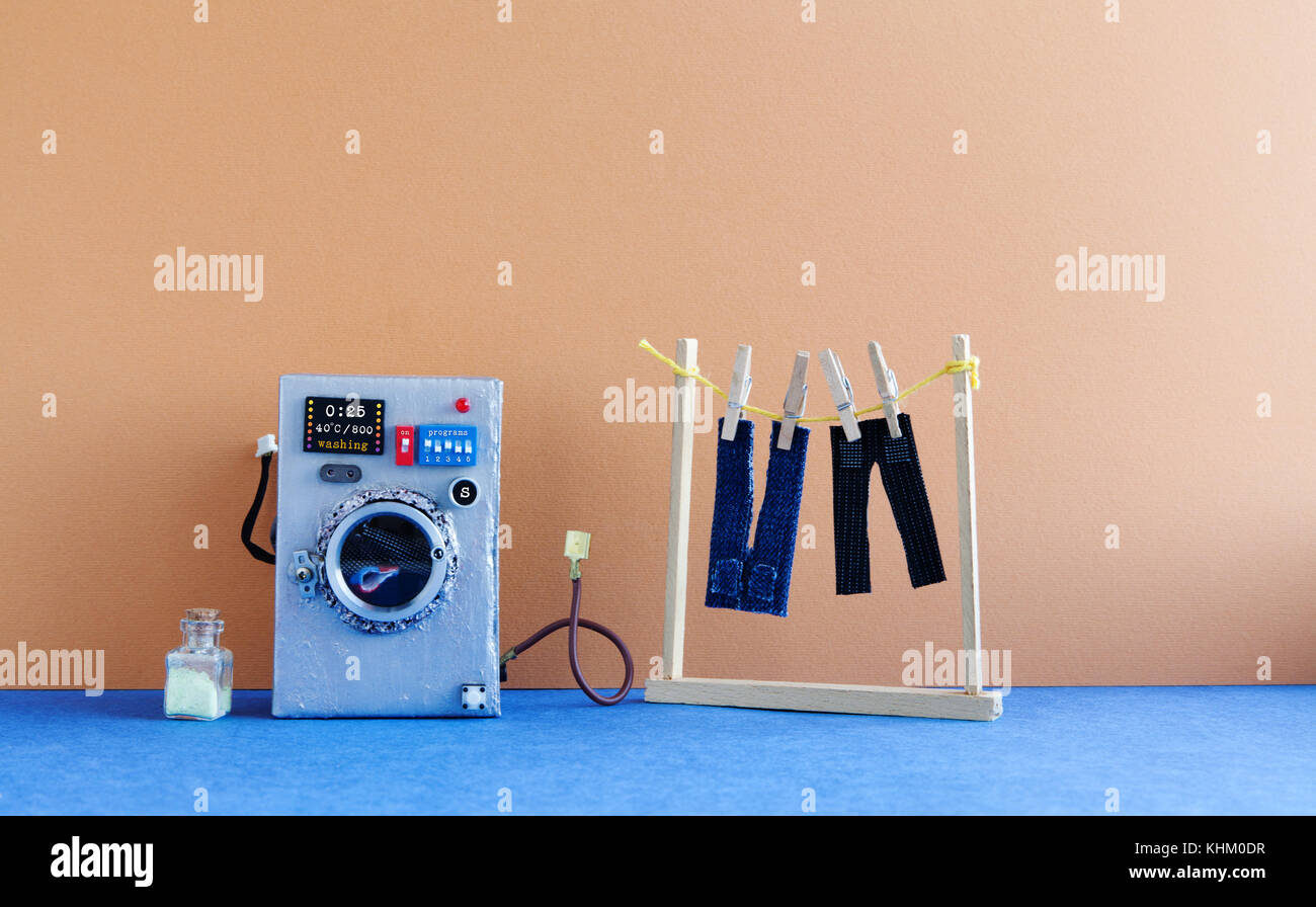 Washing machine with laundry, men's jeans pants dried on clothesline with clothespins. Brown wall interior, - Stock Image