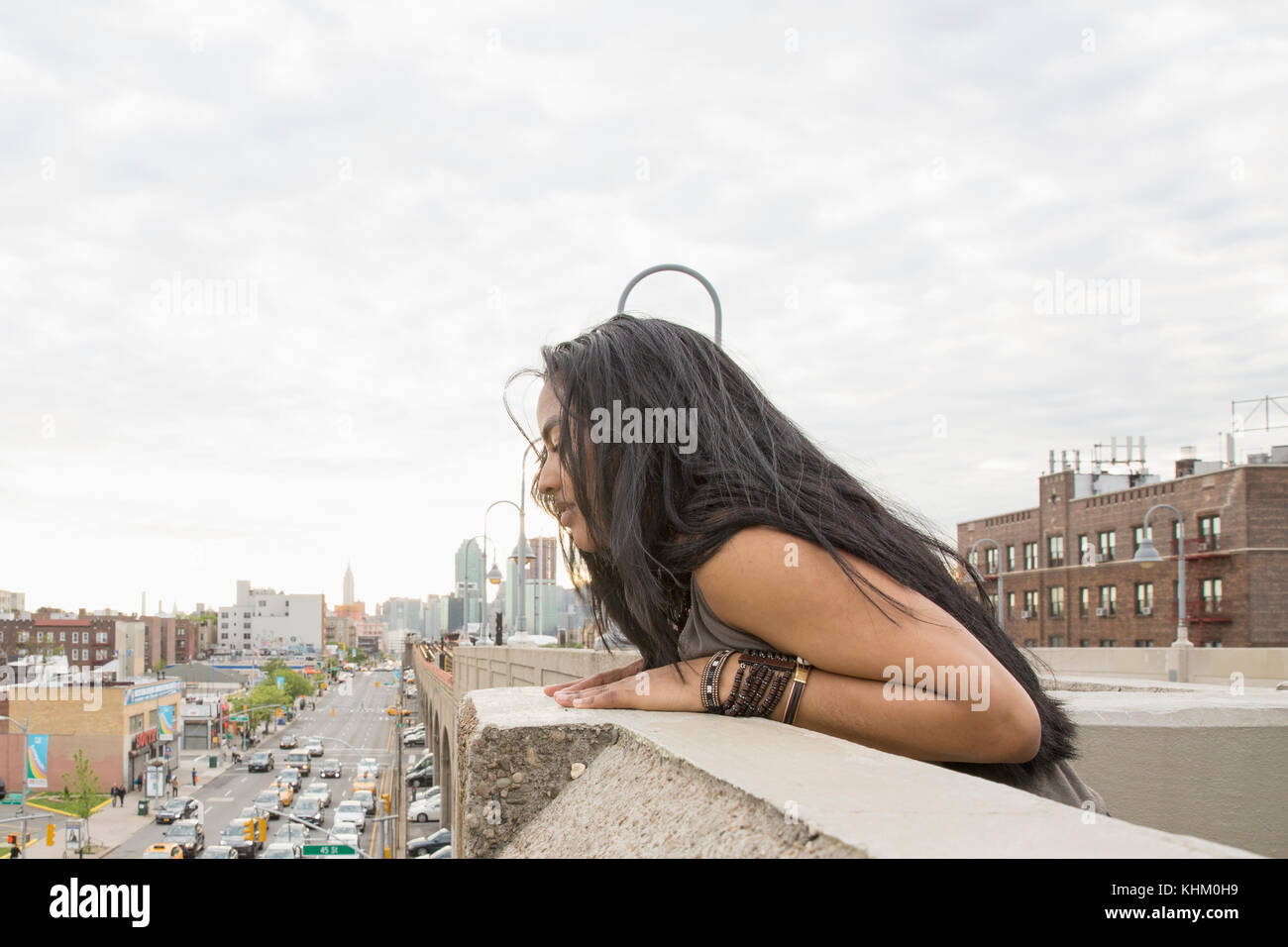Young woman leaning on a bridge in Queens, New York - Stock Image