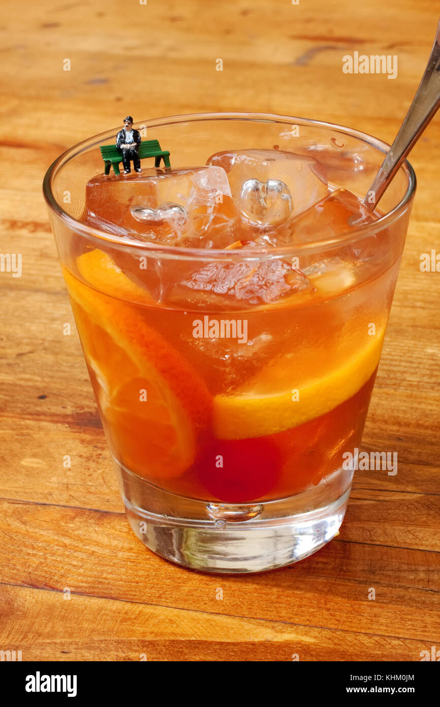 Classic Old Fashioned cocktail glass. Orange color alcohol drink, miniature figure old actor comic sitting on bench. - Stock Image