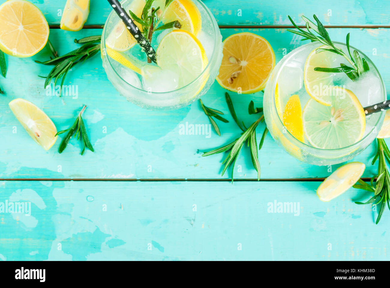 Cold lemonade or alcohol vodka cocktail with lemon and rosemary, on light blue table, copy space top view - Stock Image