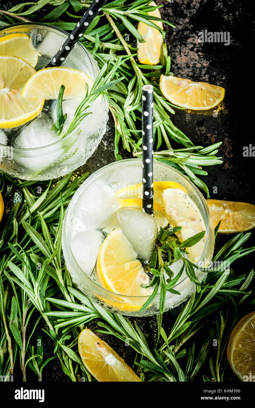 Cold lemonade or alcohol vodka cocktail with lemon and rosemary, On a black rusty metallic background, copy space - Stock Image