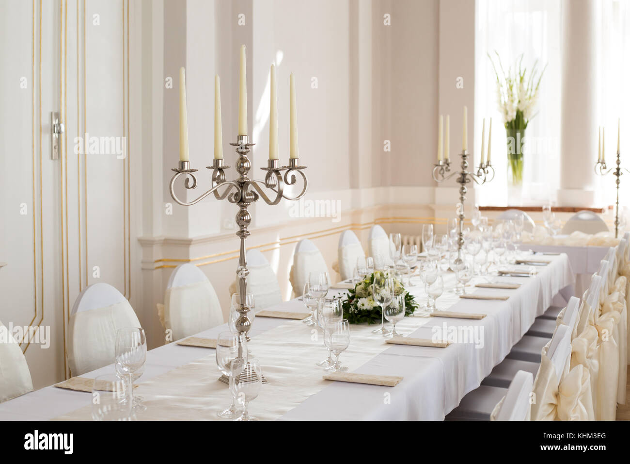 Close-up photo of chromium candlestick with five unlit white wax candles placed on the table prepared for wedding - Stock Image