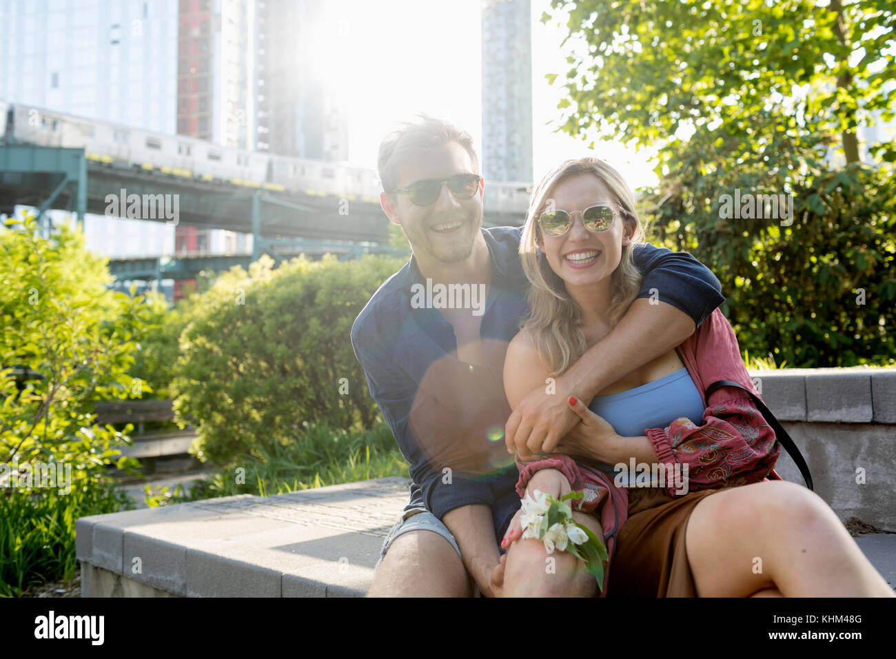 Couple sitting together in a park - Stock Image