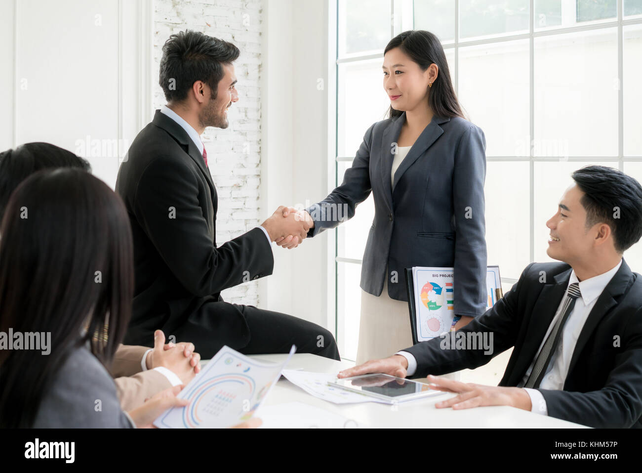 Successful job Asian businessman and businesswoman shaking hands in board room when finishing up a meeting. - Stock Image