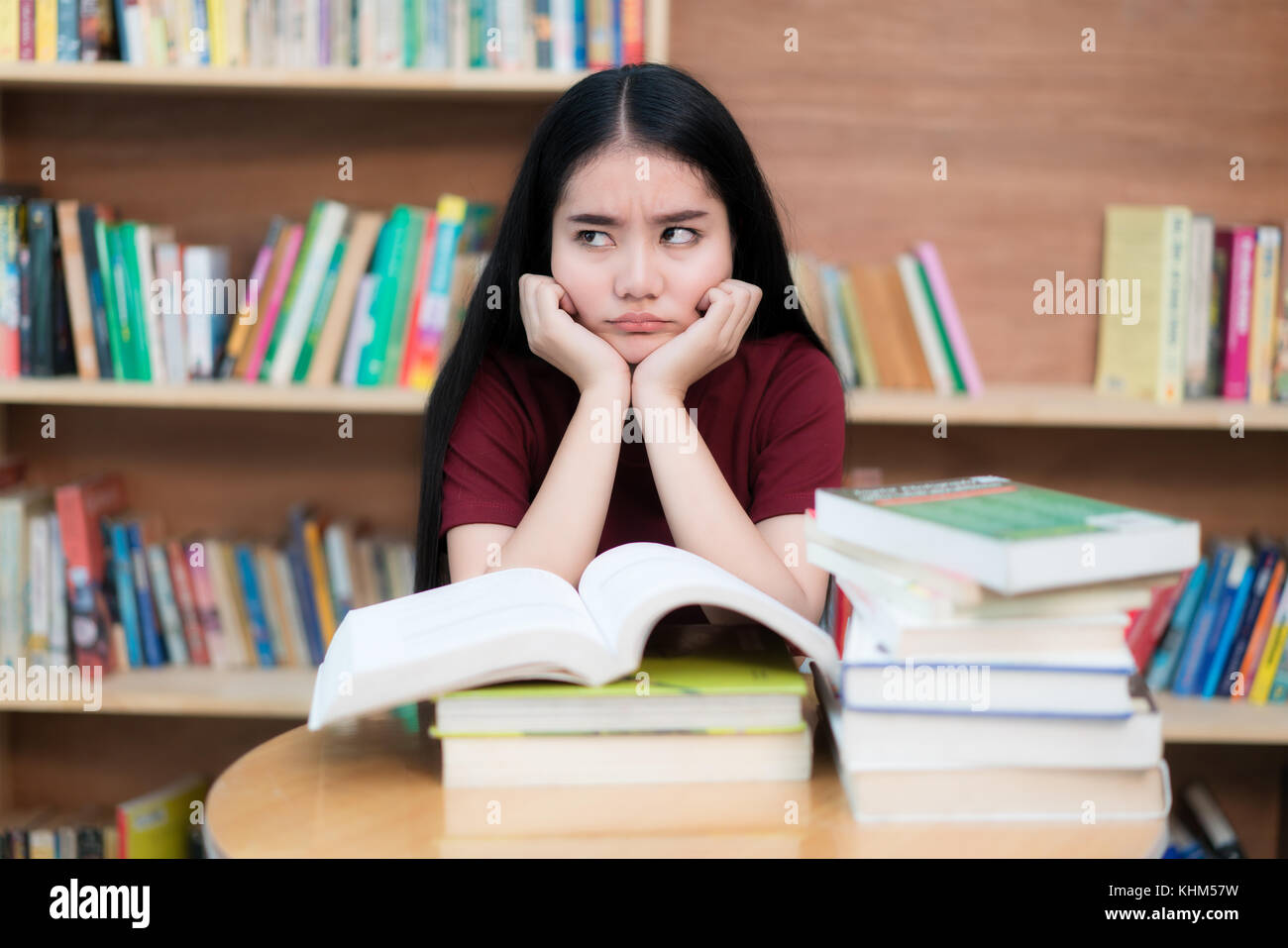 Asian woman student boring reading book at library with a lot of books in university. Asian student disheartened - Stock Image
