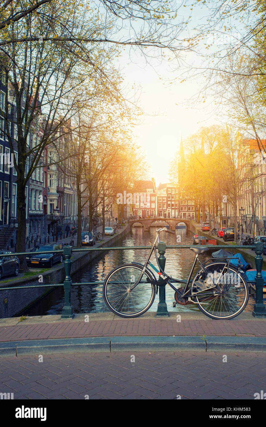 Bicycle on the bridge with Netherlands traditional houses and Amsterdam canal in Amsterdam ,Netherlands. - Stock Image