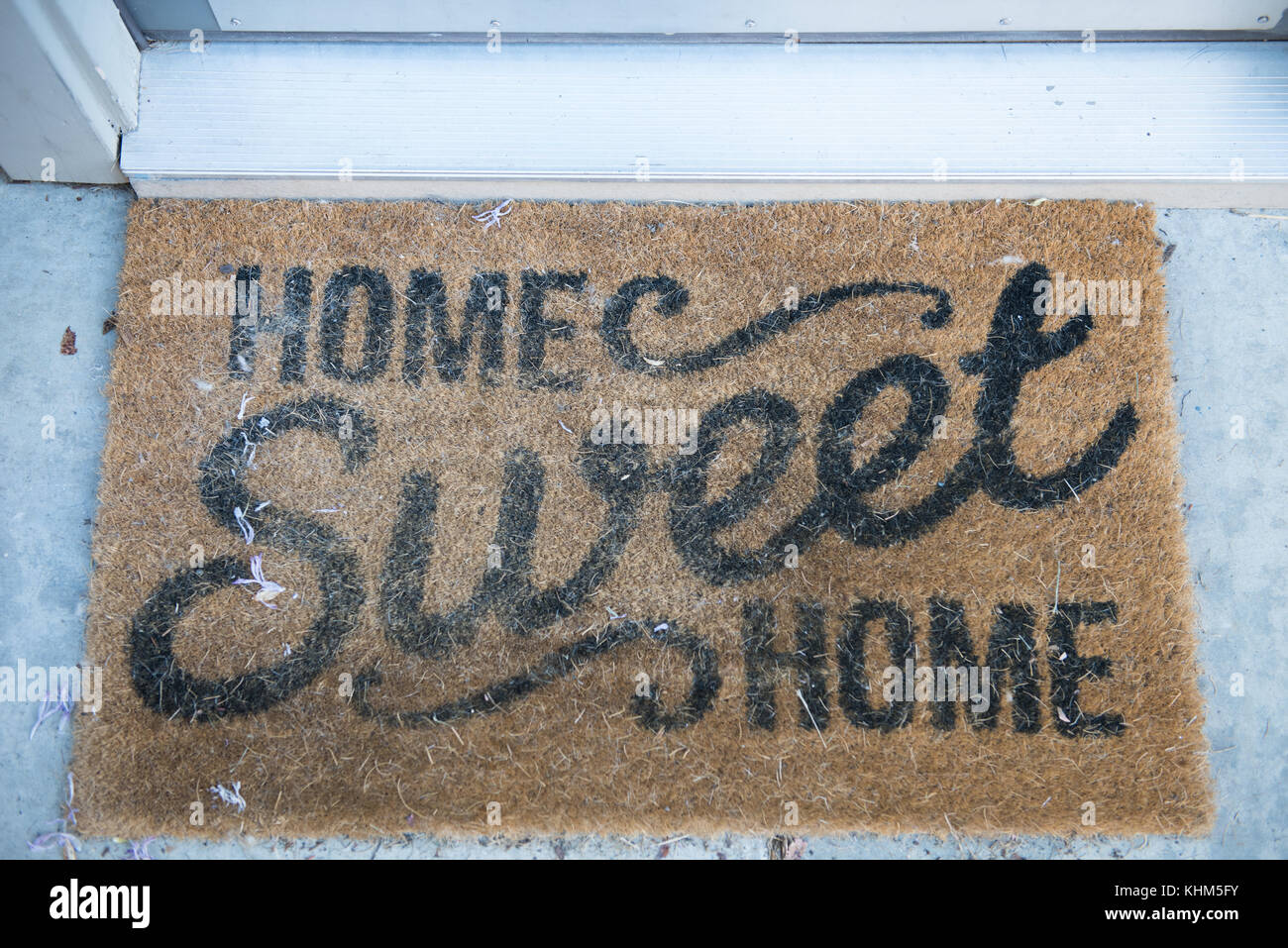 Home Sweet Home Welcome Mat in front of Doorway - Stock Image