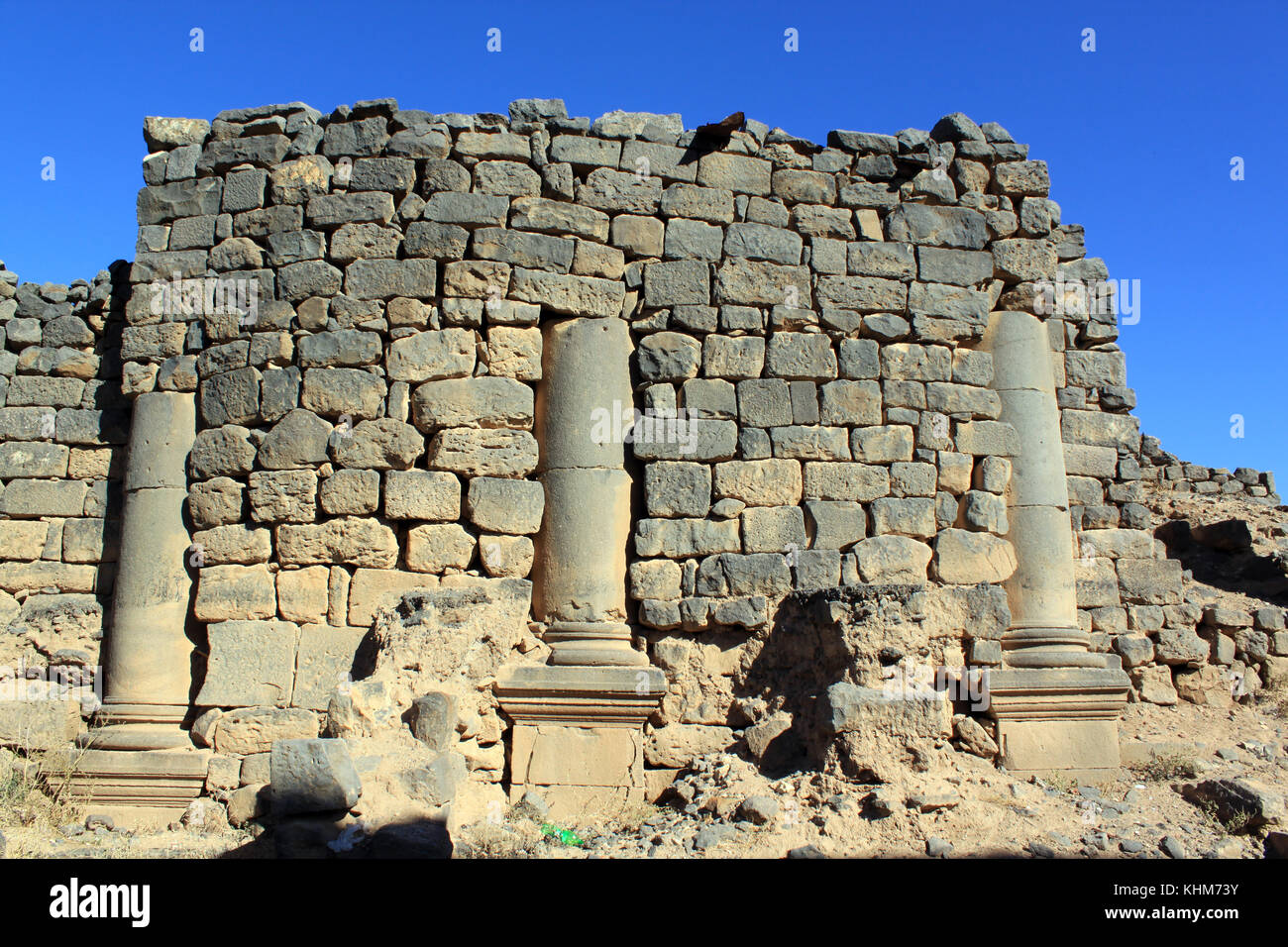 Stone basalt wall and columns on the street of Old Bosra, Syria - Stock Image