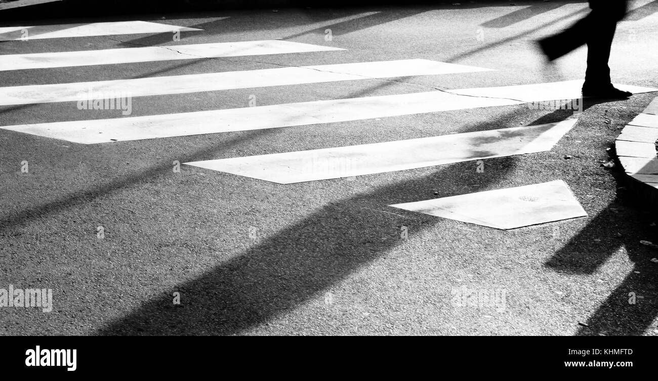 Blurry zebra crossing with silhouette and shadow of person walking in the cold and sunny early morning autumn day - Stock Image