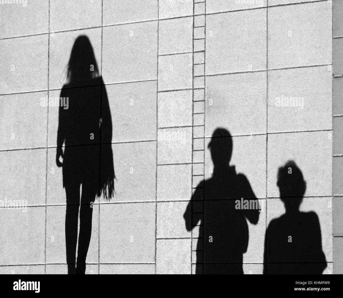Shadow of parents and teenage daughter , on city sidewalk from above - Stock Image