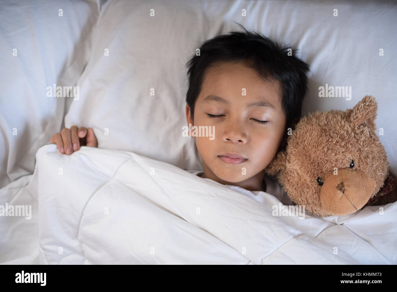 boy sleeping on bed with teddy bear white pillow and sheets.boy fall asleep in morning.sleep concept - Stock Image