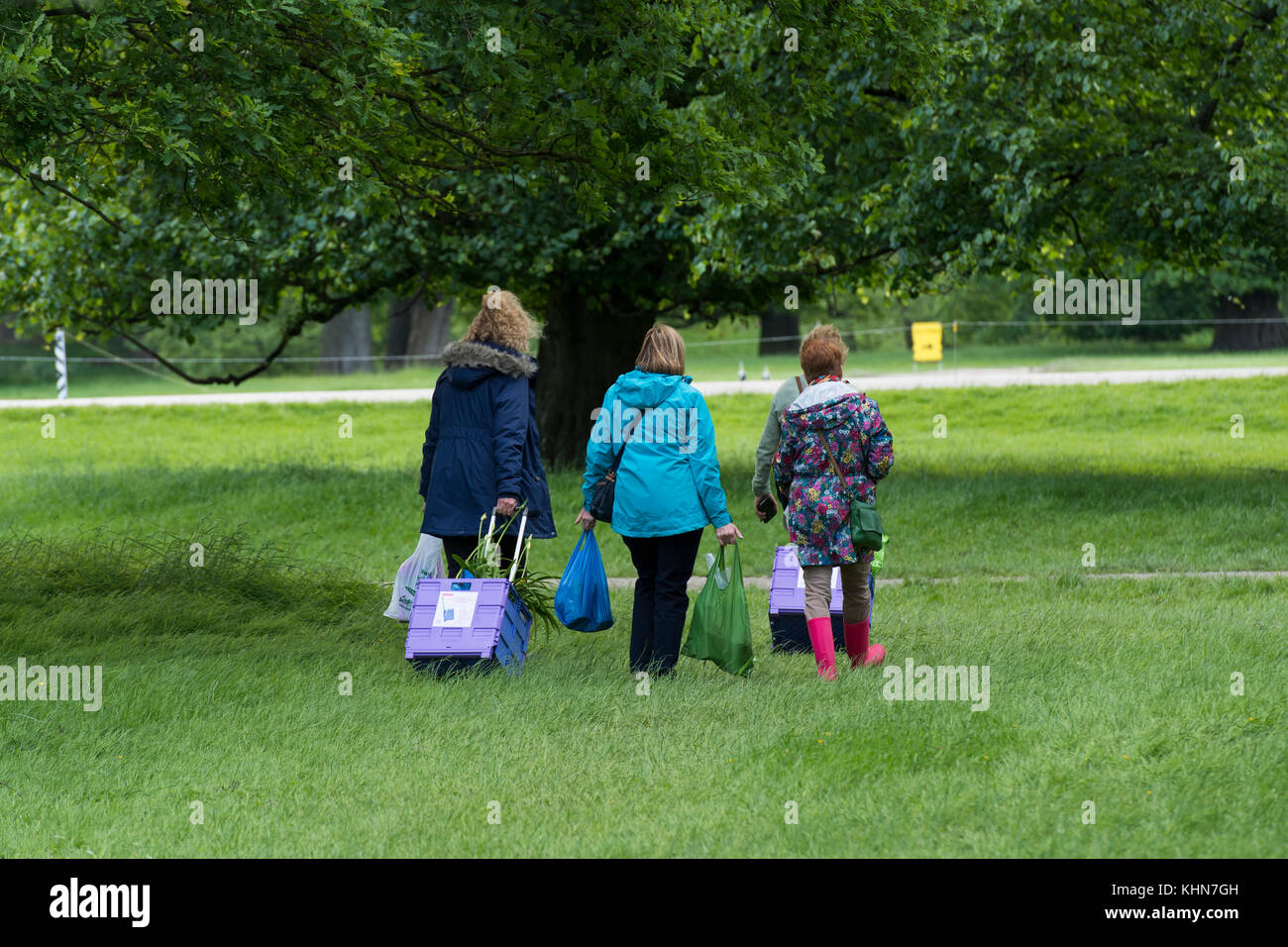Time to go home for people walking & leaving showground with bags & folding shopping trolleys - RHS Chatsworth - Stock Image
