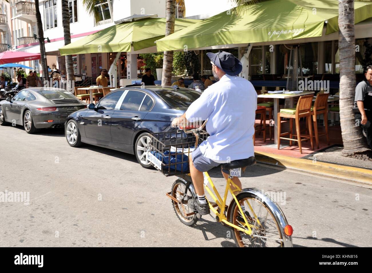 United States Post Office (USPS) postal worker, postman, delivering mail on bicycle in South Beach, Miami, Florida, - Stock Image