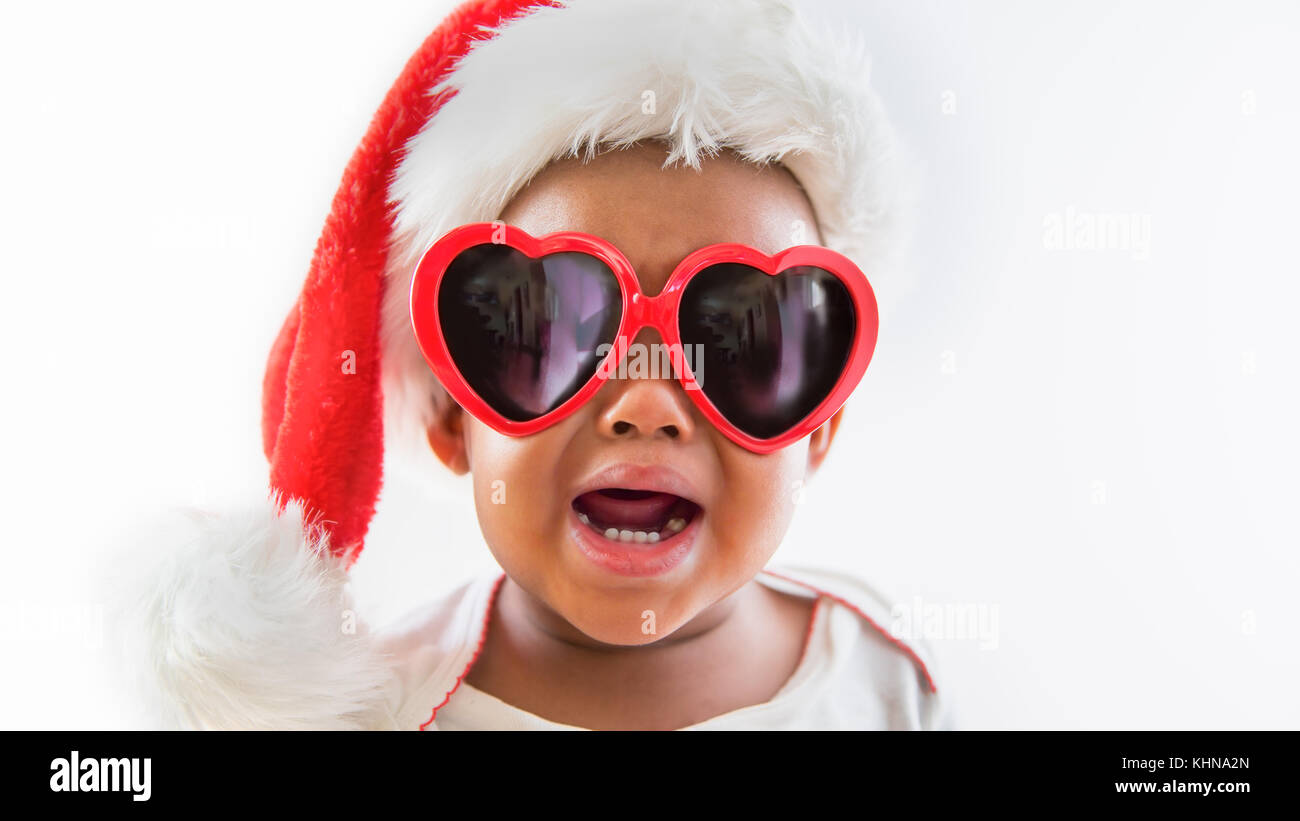 Funny closeup portrait of upset Black African American baby wearing heart sunglasses and Santa hat on white background Stock Photo