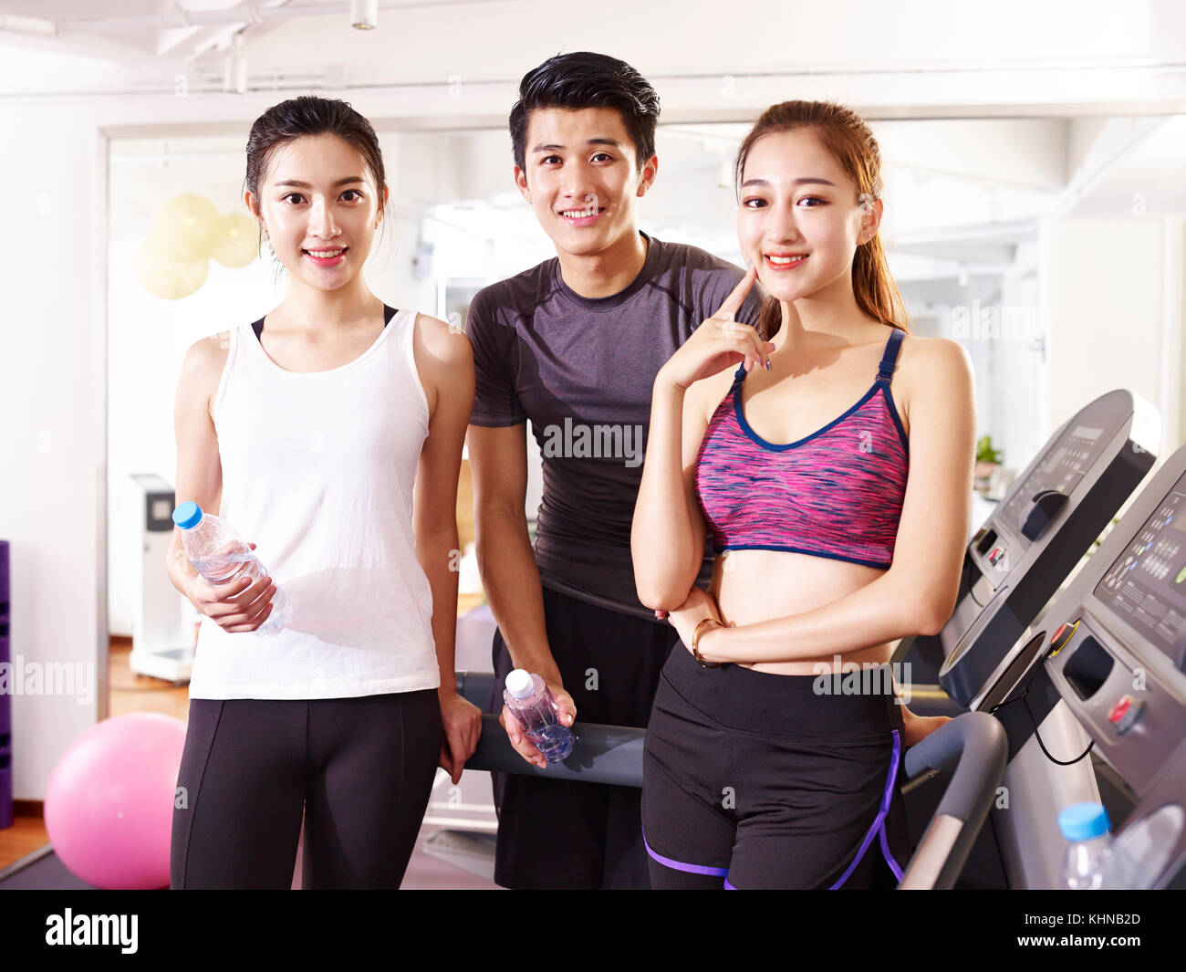 portrait of three happy young asian adult in fitness center. - Stock Image