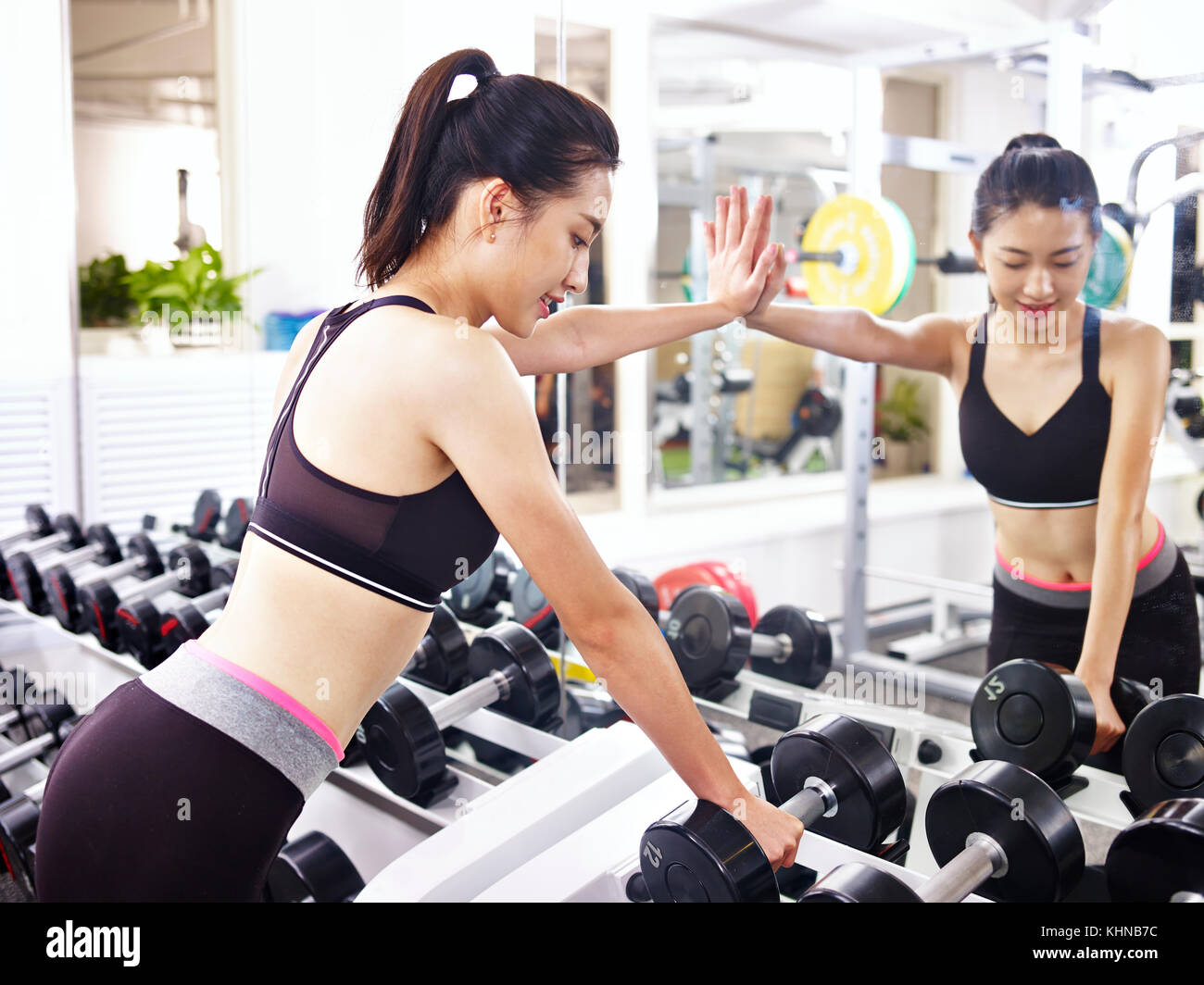 young asian woman working out in fitness center. - Stock Image
