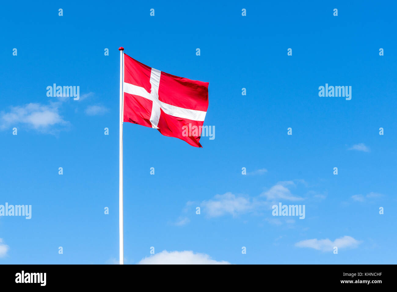 The danish flag in red and white waving in the wind on a flagstaff with a blue sky in the background - Stock Image