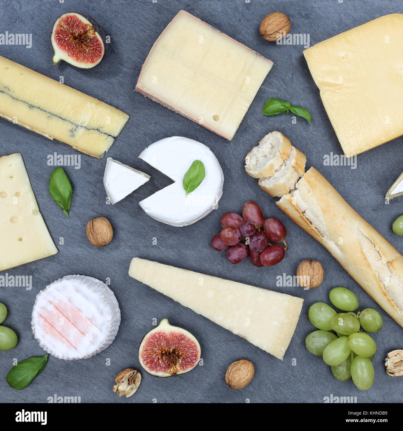 Cheese board platter plate Swiss bread Camembert square slate top view from above - Stock Image