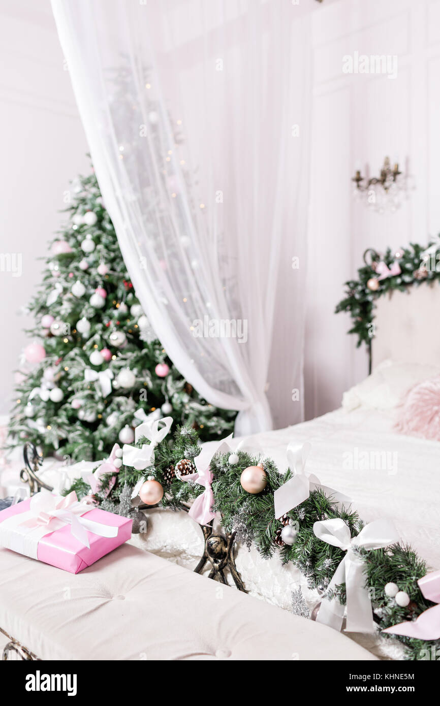 Cozy Christmas home interior. New year decoration. bright bedroom room with large double bed. - Stock Image