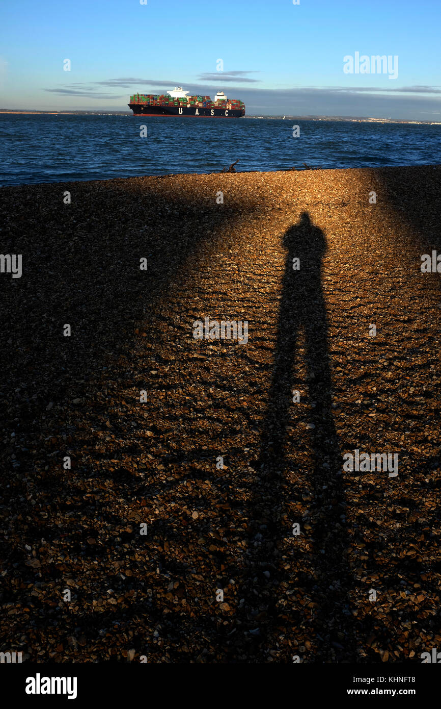 Shadow, of, man, taking, photographer, on, beach, with ,container, ship, on sea, in background, Cowes, Isle of Wight, - Stock Image