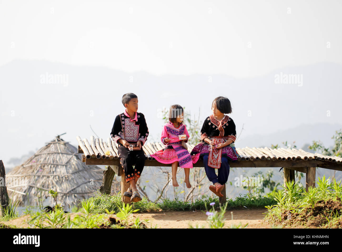 Lovely boy and girl playing outdoors while posing wearing ethnic clothes from the Hmong tribe, indigenous people of Thailand. Stock Photo