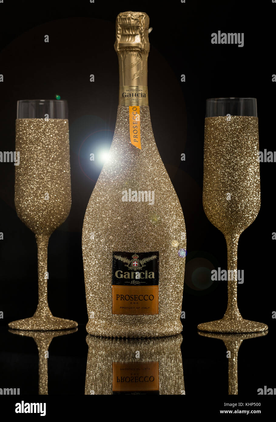 24953bb17b08 Sparkly gold glitter sprayed Prosecco bottle and champagne flute glasses  with lens flare