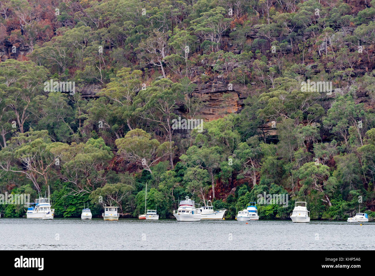 Boats moored in a quiet waterway to the north of Sydney with a backdrop of a sandstone cliff and gum trees. - Stock Image