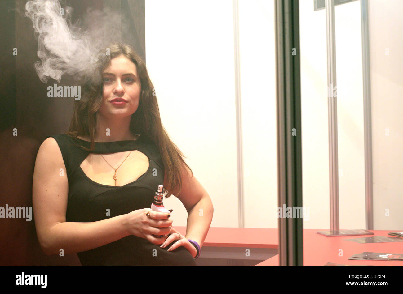 Young urban hipster girl smoking vape at the stand promoting electronic cigarettes. Vape&Trade Expo. March 19, - Stock Image