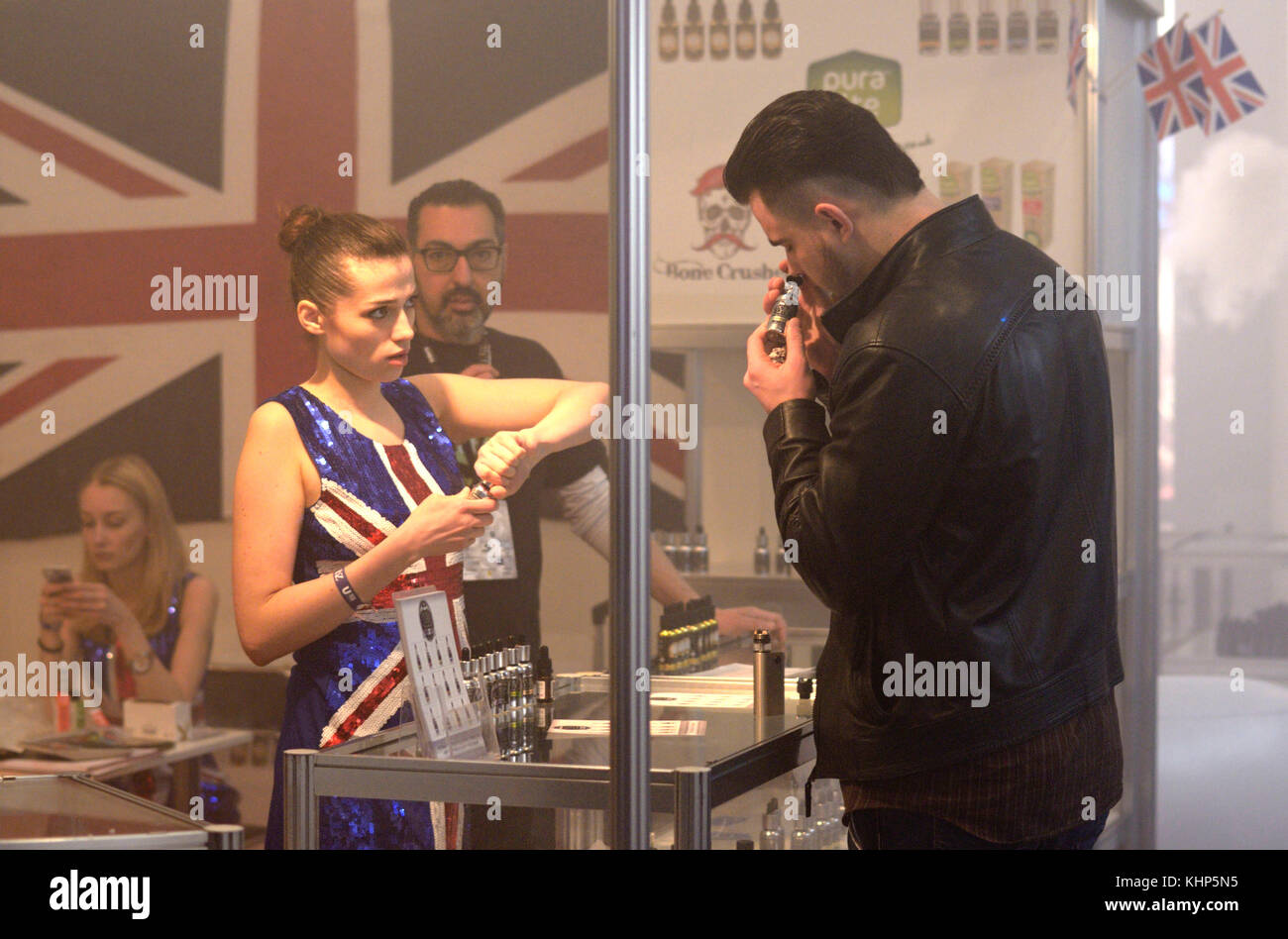 Man smelling vape flavour from a bottle and a girl going to give him another one. Vape&Trade Expo. March 19, - Stock Image
