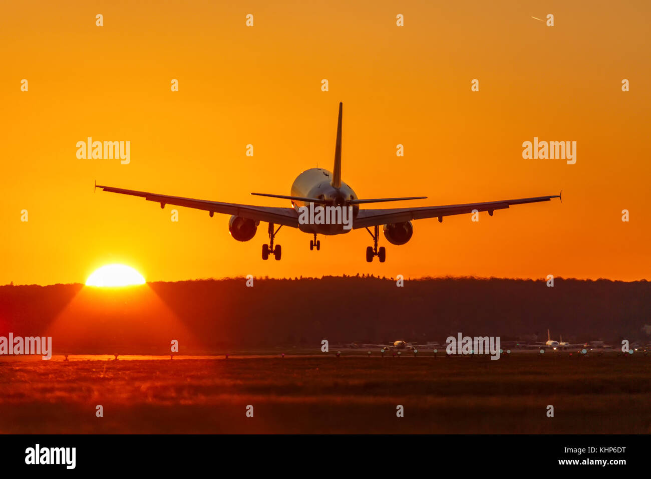 Airplane landing flying airport sun sunset vacation holidays travel traveling plane aircraft travelling - Stock Image