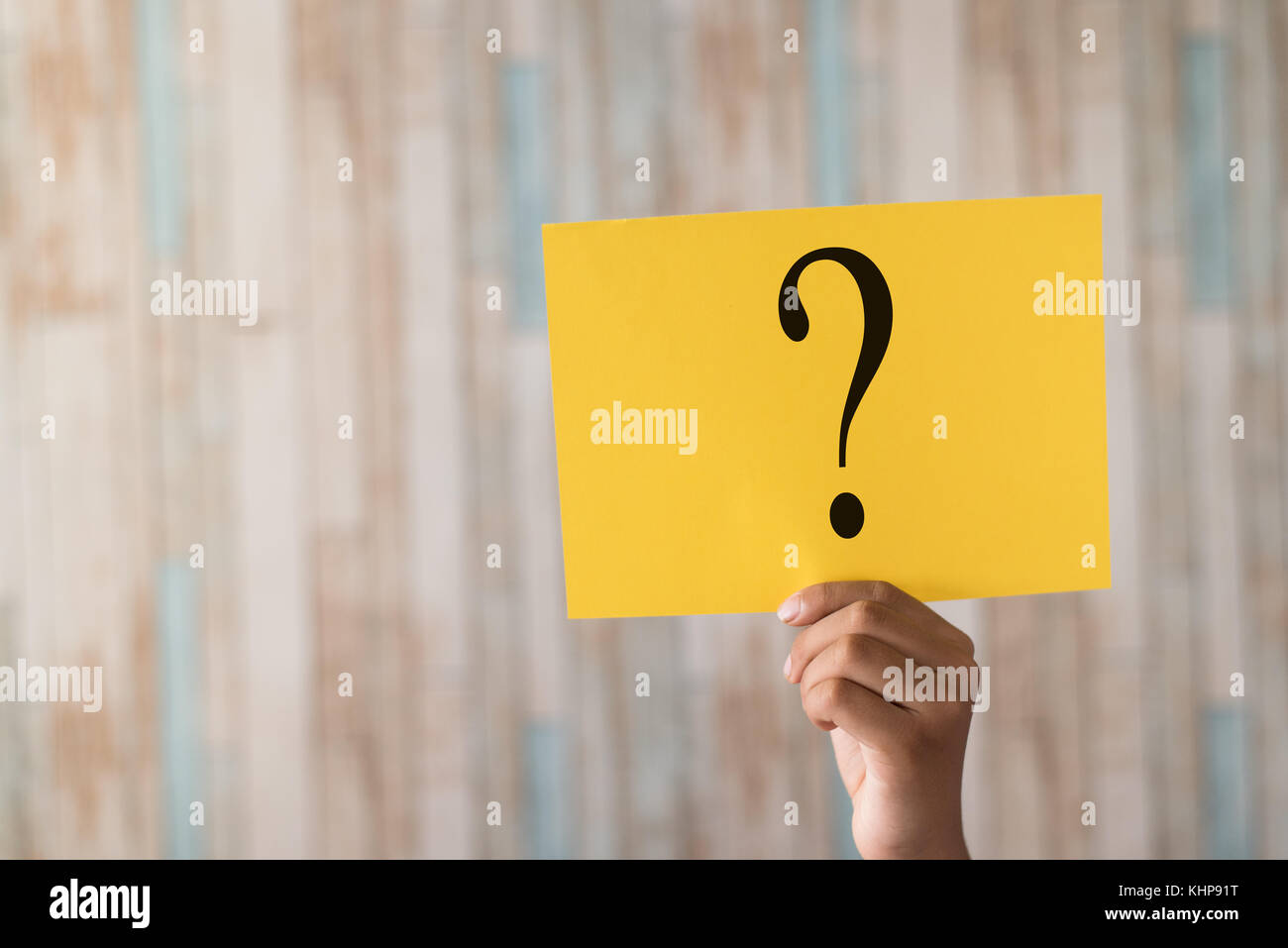 hand holding a paper note with question mark.question mark written on paper - Stock Image