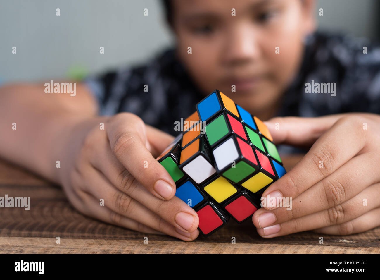 asian boy playing with rubik's cube.boy solving puzzle.brain teaser toy - Stock Image
