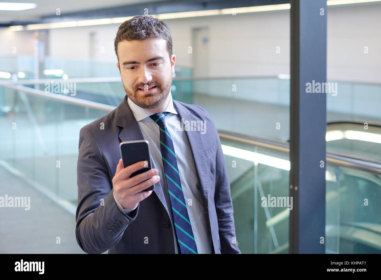 Businessman is looking at his mobile phone while is going to work - Stock Image