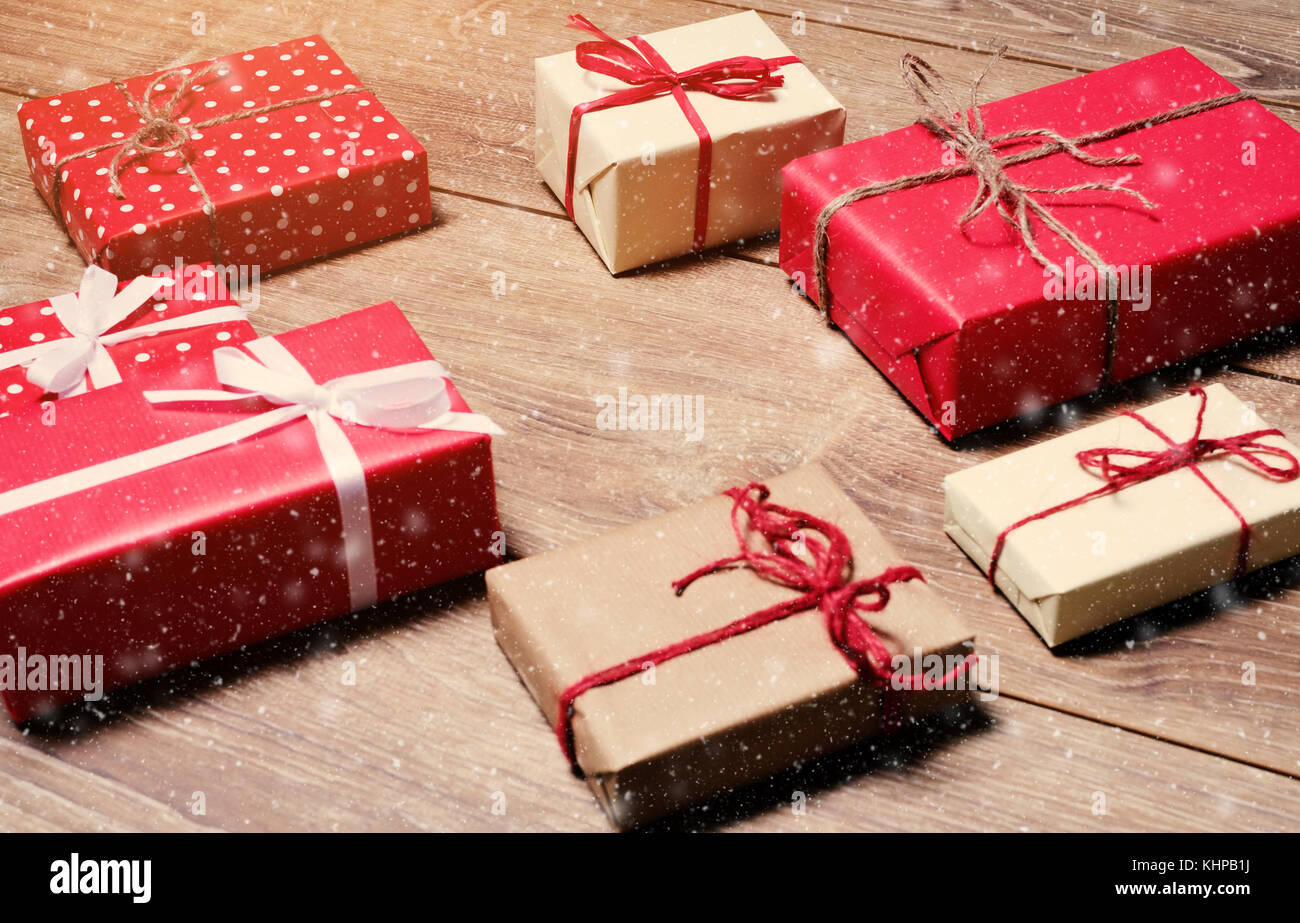 Christmas presents boxes laid on a wooden table and falling snowflakes - Stock Image