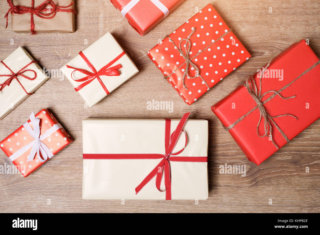Christmas presents boxes laid on a wooden table background - Stock Image