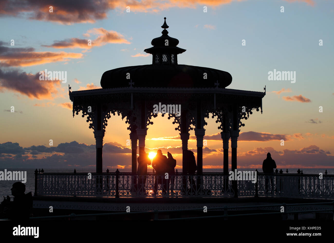 The setting sun silhouettes the Bandstand on Brighton seafront. Stock Photo