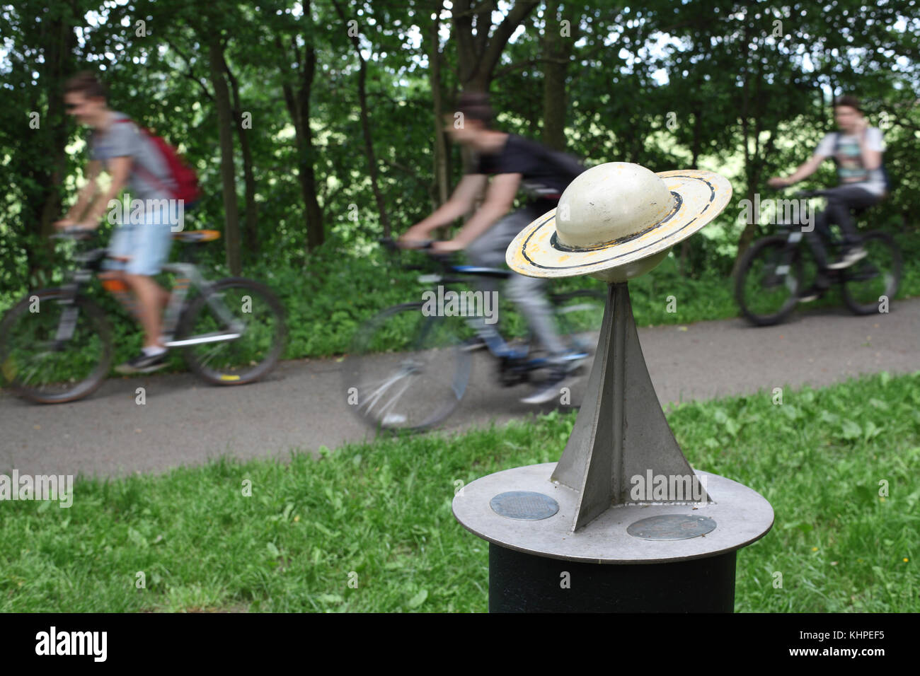 Cyclists pass a model of the planet Saturn, on the York to Selby cycle path - the location of a 10.4 km scale model - Stock Image