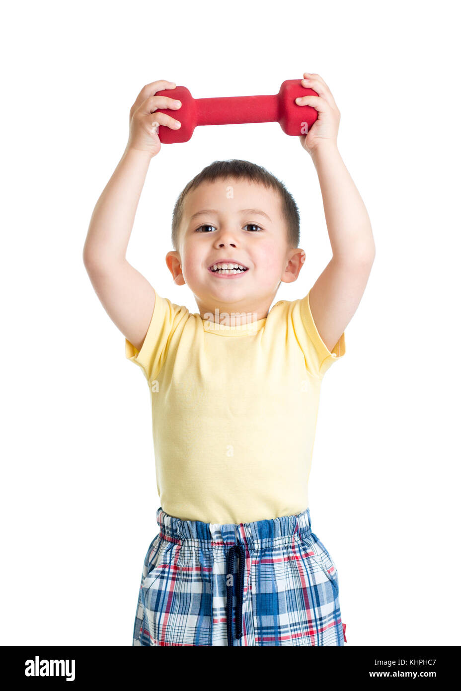 Child boy is engaged in physical training with red dumbbell - Stock Image