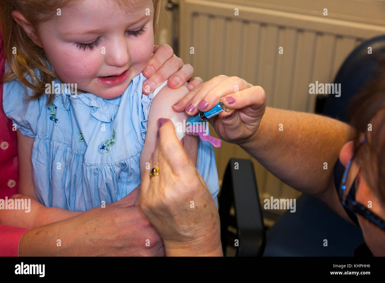 Practice nurse giving NHS 4-in-1 pre-school booster / Pre school booster & MMR second dose immunisation / inoculation - Stock Image