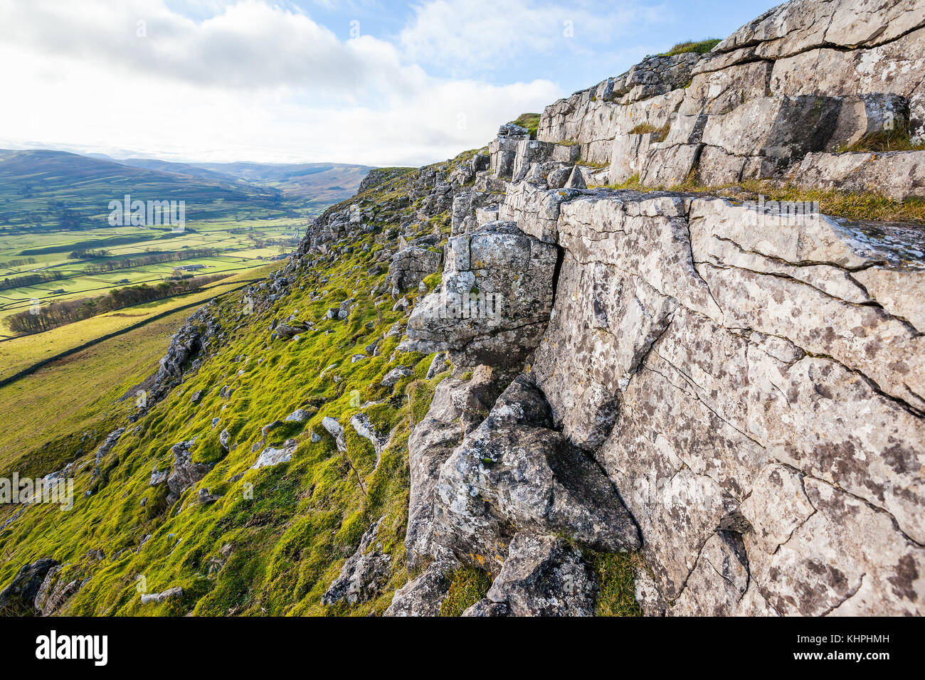 Rocky cliff with weathered limestone on Stags Fell in the Yorkshire Dales, England. Valley of Wensleydale can be - Stock Image