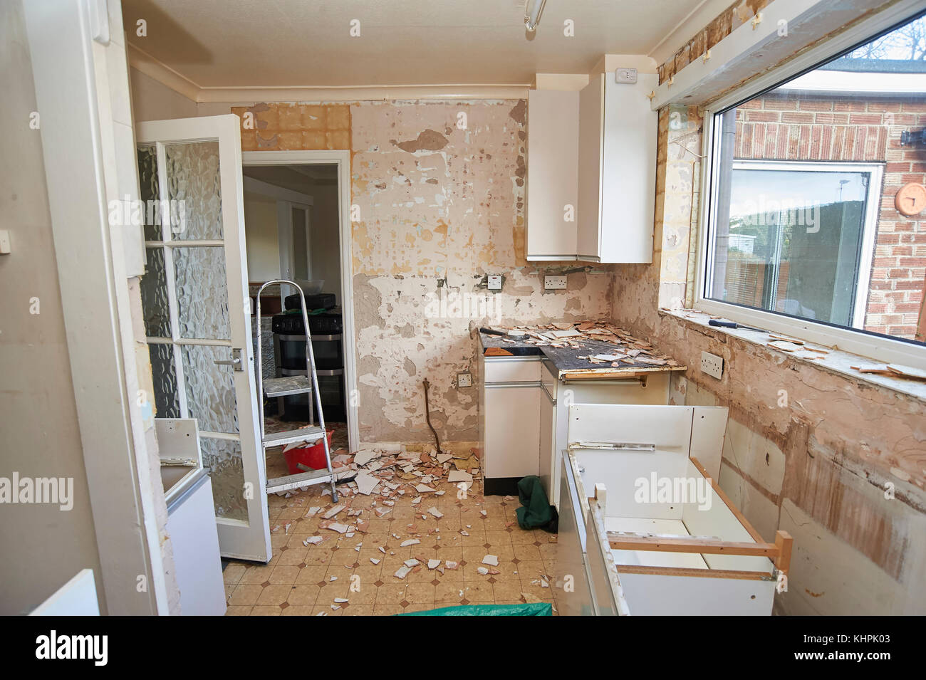 Residential property renovation, dismantling kitchen units and removing wall tiles - Stock Image