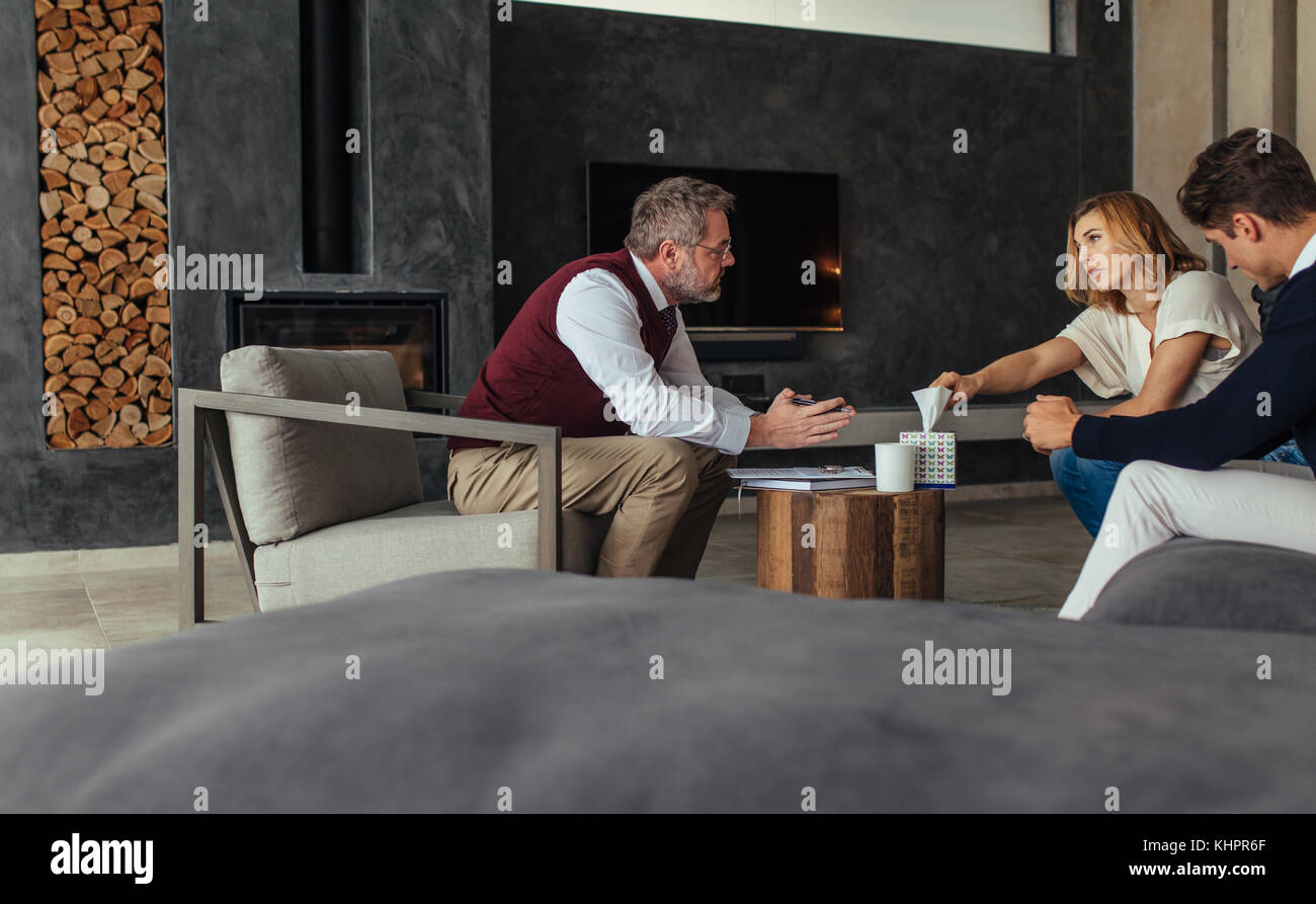 Couple seeing a psychotherapist to solve their relationship problems. Sad woman taking a tissue paper during the - Stock Image