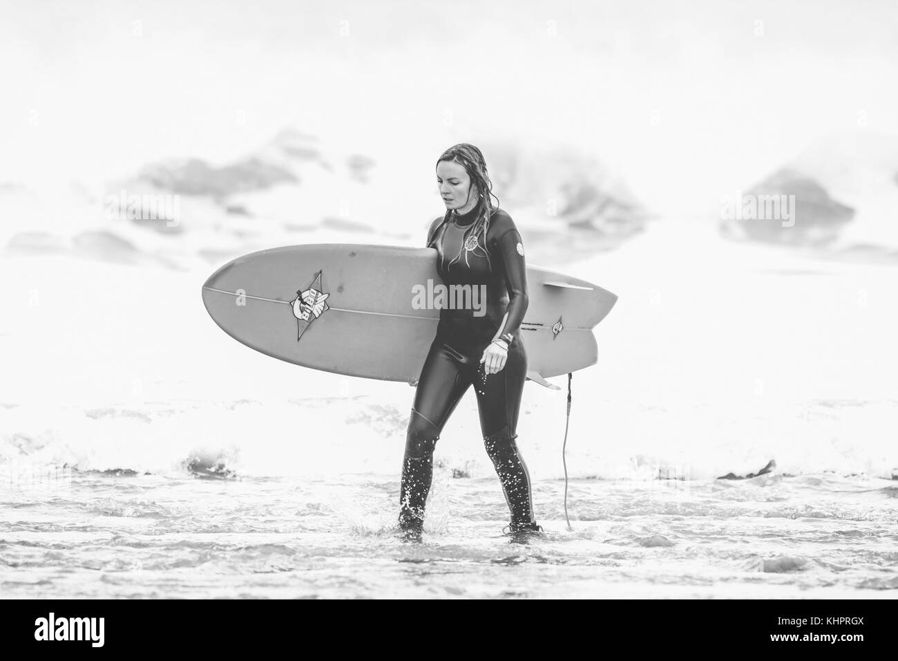 Female walking with surfboard under her arm on the beach in Cornwall, England, UK - Stock Image