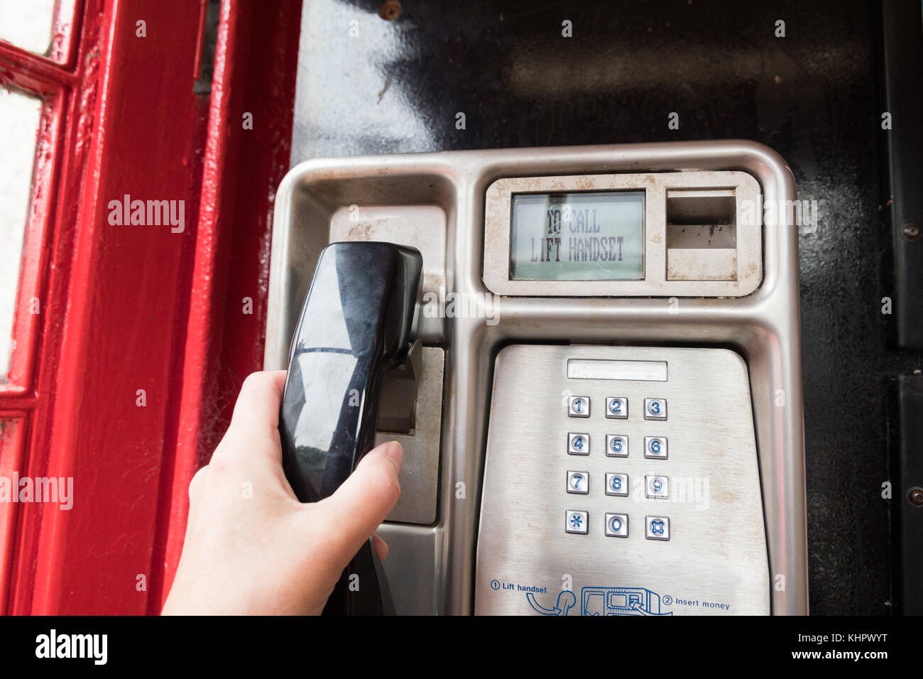 using a BT payphone in red telephone box - Stock Image