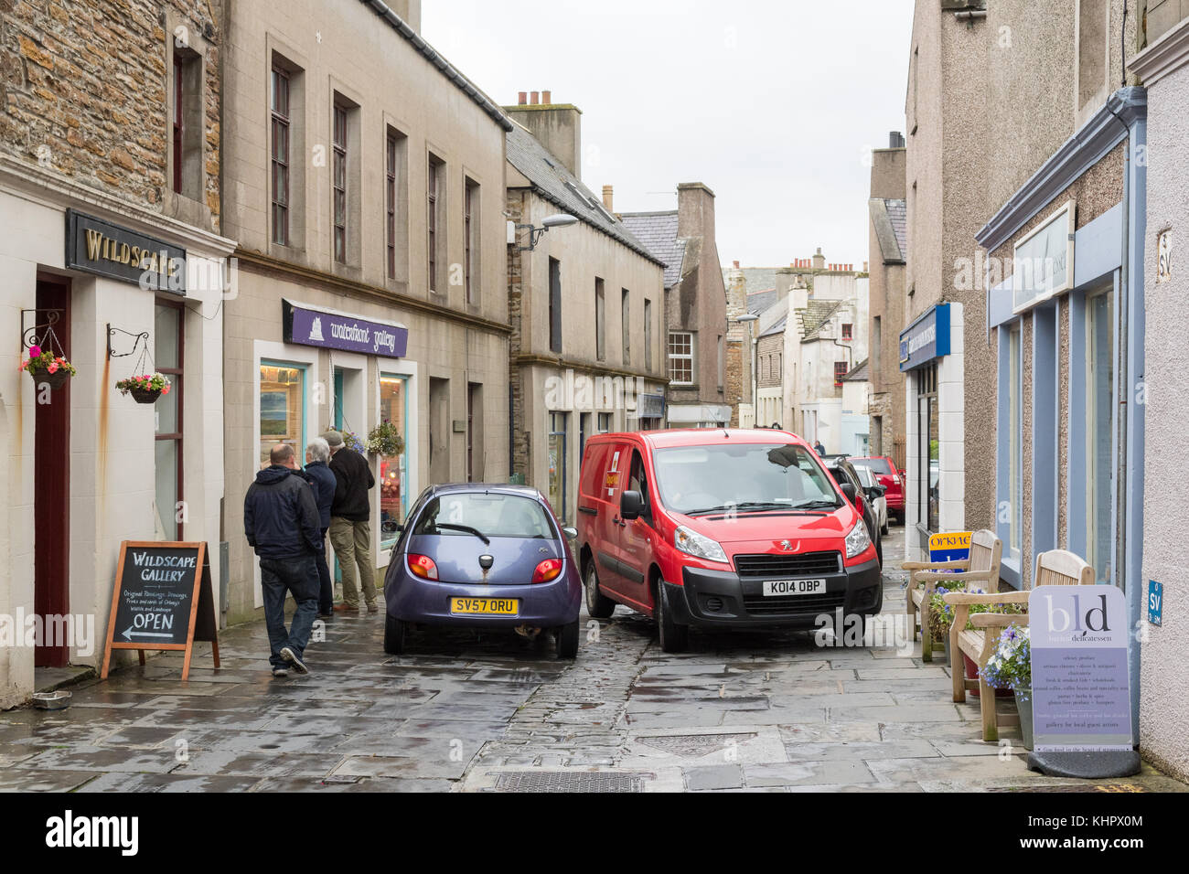 Cars passing amongst shoppers in narrow main shopping street - Victoria Street - in Stromness, Orkney Mainland, - Stock Image