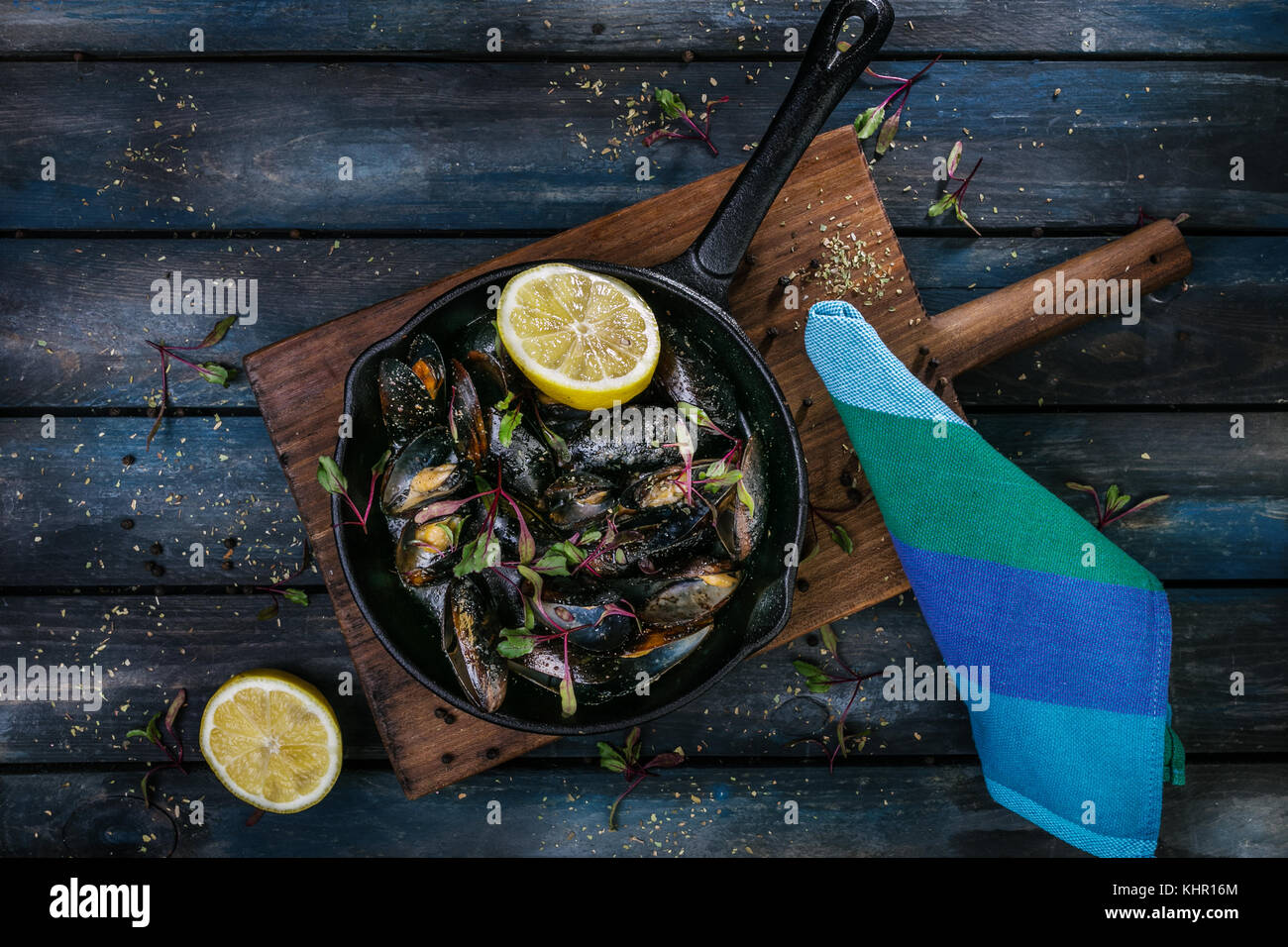 Delicious mussels. Serving on a hot frying pan with herbs spices and lemon on a colored wooden background. Top view. - Stock Image