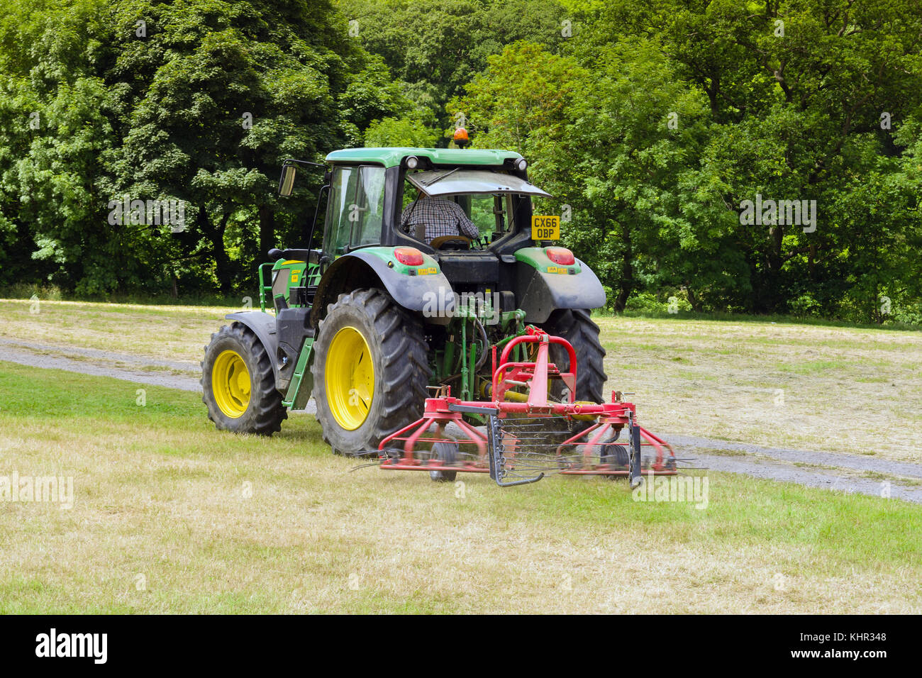 John Deere tractor working in a field with a twin rotor hay turner or tedder attachment a device for turning cut - Stock Image