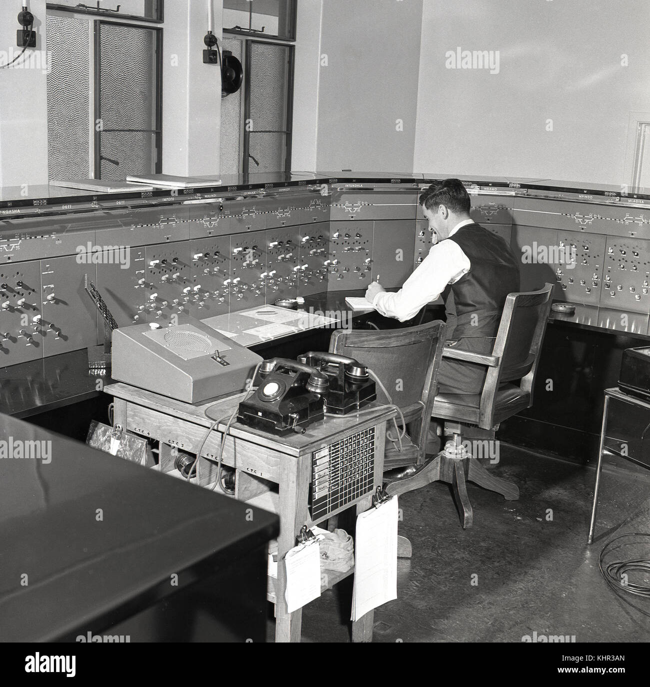 1950s, historical, male railway signal operator sitting at the control desk, Rhodesia, Africa. The signal equipment - Stock Image