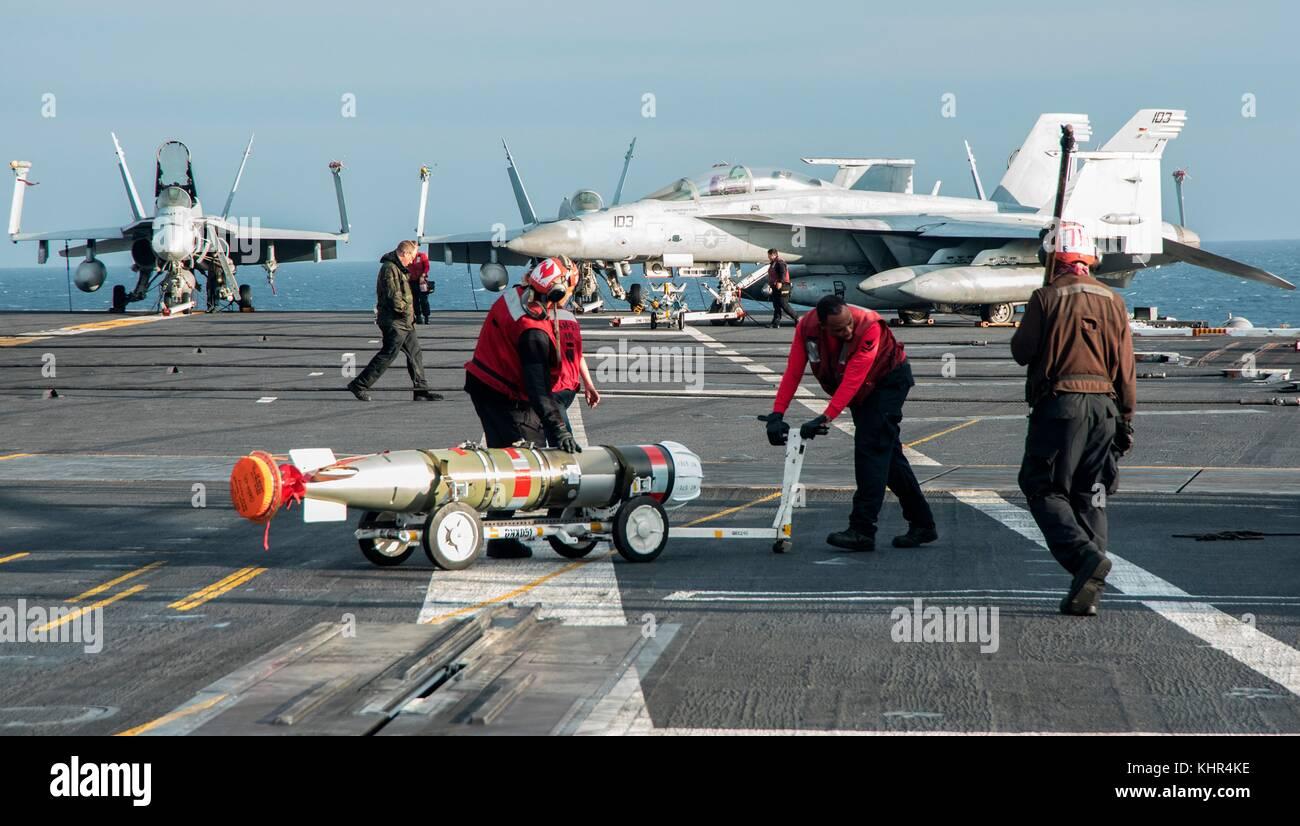 U.S. Navy sailors move a MK 54 REX torpedo across the flight deck aboard the U.S. Navy Nimitz-class aircraft carrier - Stock Image