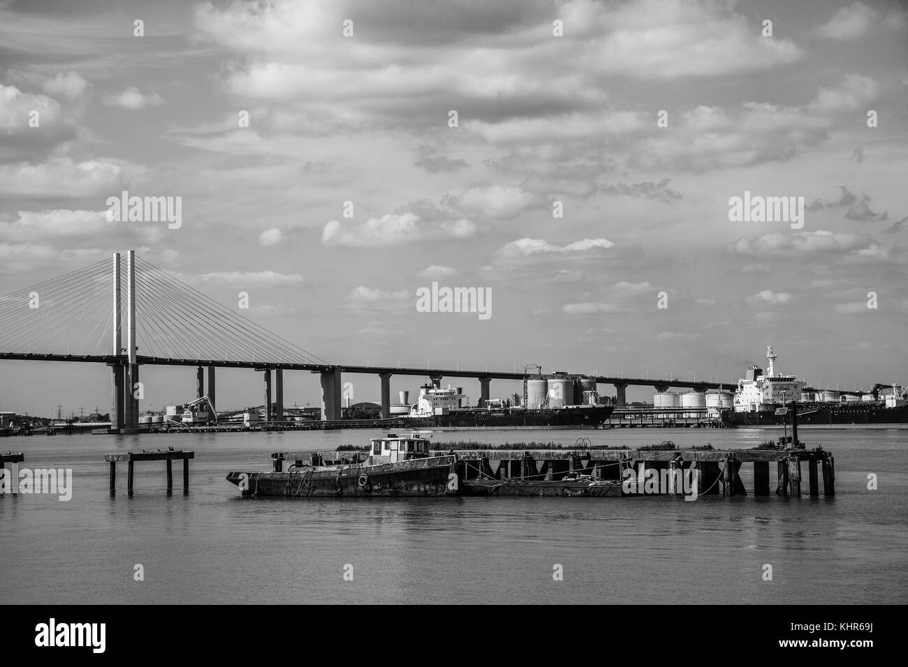 QEII Bridge over the River Thames with barges in foreground, mono - Stock Image